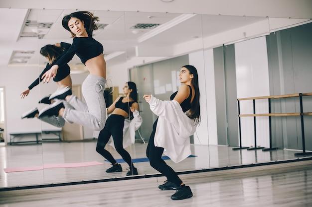 Duas belas meninas delgadas fazendo dança e ginástica no salão de dança Foto gratuita
