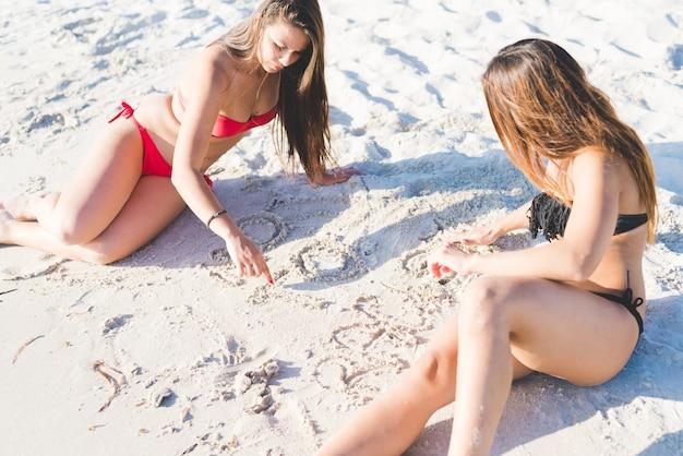 Duas belas moças deitada na areia na praia Foto Premium