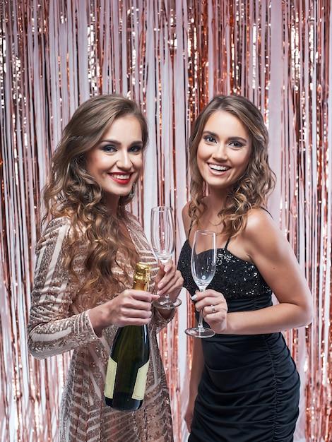 Duas belas mulheres elegantes, bebendo champanhe contra decoração brilhante Foto Premium