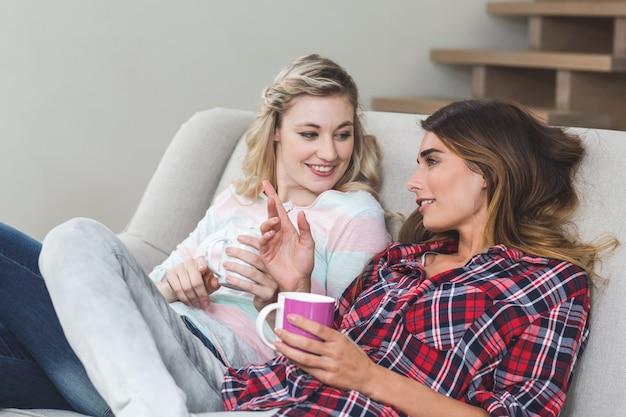 Duas belas mulheres segurando uma xícara de café e conversando na sala de estar Foto Premium
