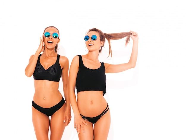 Duas belas mulheres sorridentes sexy em lingerie preta. modelos quentes na moda se divertindo. meninas isoladas em óculos de sol Foto gratuita