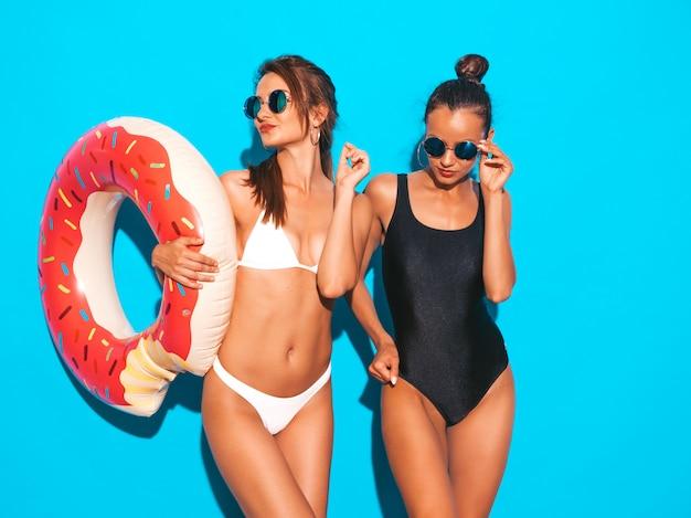 Duas belas mulheres sorridentes sexy em trajes de banho branco e preto de verão. garotas de óculos de sol. modelos positivos se divertindo com colchão inflável donut lilo. isolado na parede azul Foto gratuita