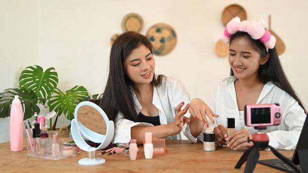 Duas blogueiras adolescentes apresentando produtos de beleza e vídeos ao vivo nas redes sociais. Foto Premium