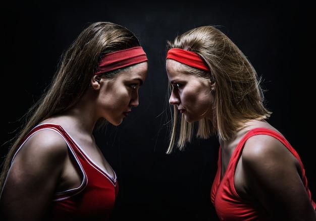 Duas boxers femininas em sportswear vermelho em pé frente a frente. esporte de luta e conceito de arte marcial Foto Premium