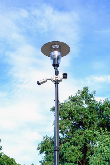 Duas câmeras de vigilância brancas no poste de luz de metal no céu azul Foto Premium