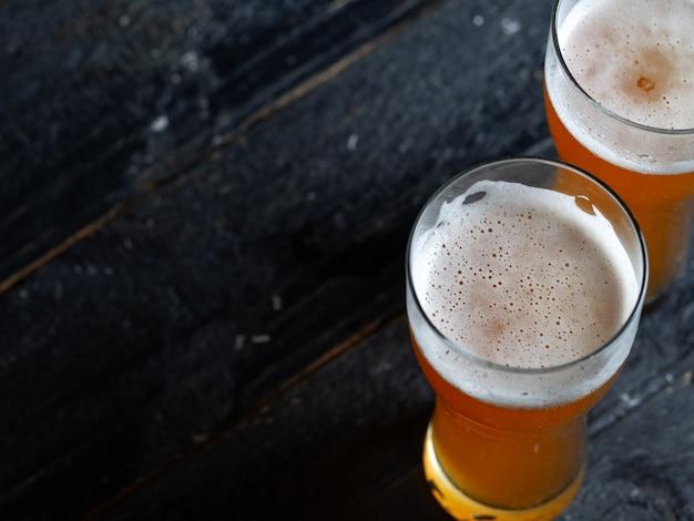 Duas cervejas geladas em um copo em uma mesa de madeira com fundo copyspace Foto Premium