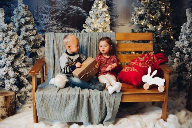 Duas crianças brincando com o natal perto de decoração e árvore de natal Foto Premium