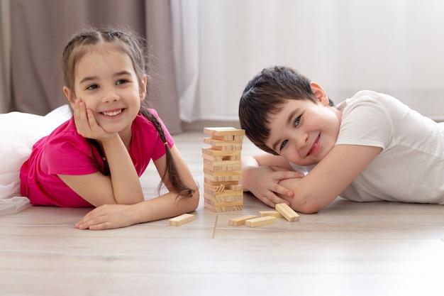 Duas crianças brincando de jogo de madeira no chão a sorrir. Foto Premium