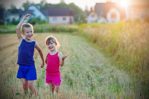Duas crianças felizes em pé no campo de trigo. Foto Premium