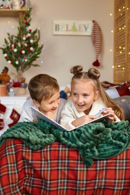 Duas crianças fofas e felizes escrevendo uma carta para o papai noel Foto Premium