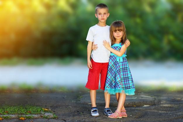 Duas crianças irmão e irmã juntos. garota de vestido menino abraço. conceito de relações familiares. Foto Premium