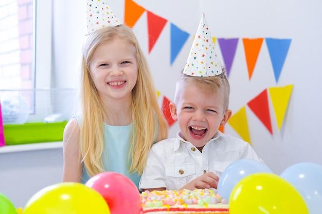Duas crianças loiras caucasianos menino e menina se divertindo e rindo na festa de aniversário. fundo colorido com balões e bolo arco-íris de aniversário. Foto Premium