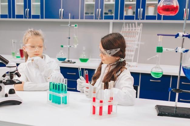 Duas crianças no jaleco aprendendo química no laboratório da escola. jovens cientistas em óculos de proteção fazendo experimento em laboratório ou gabinete de químico. estudando ingredientes para experimentos. Foto Premium