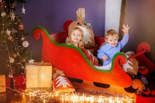 Duas crianças pequenas perto com uma árvore de natal Foto Premium