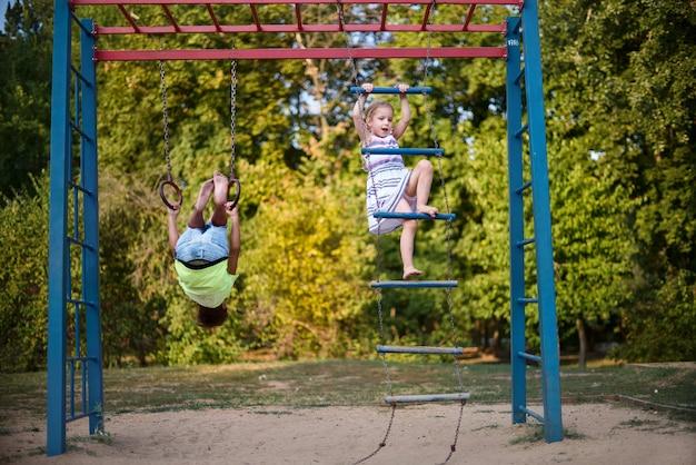 Duas crianças sorridentes felizes estão exercitando em um campo de esportes. Foto Premium