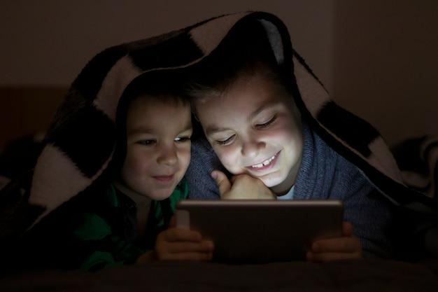 Duas crianças usando tablet pc sob cobertor durante a noite. irmãos bonitos com tablet computador em um quarto escuro sorrindo. Foto gratuita