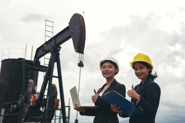 Duas engenheiras estão ao lado de trabalhar as bombas de óleo com um céu branco. Foto gratuita