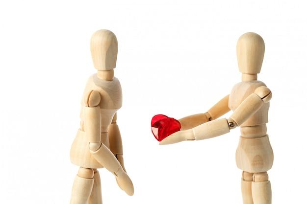 Duas figuras de madeira de um boneco dão um coração vermelho Foto Premium