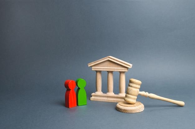 Duas figuras de oponentes estão perto do tribunal e do martelo do juiz. resolução de conflitos Foto Premium
