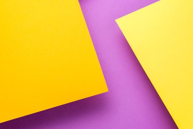 Duas folhas de papel amarelo e laranja sobem acima do fundo roxo. as folhas lançam uma sombra. Foto Premium