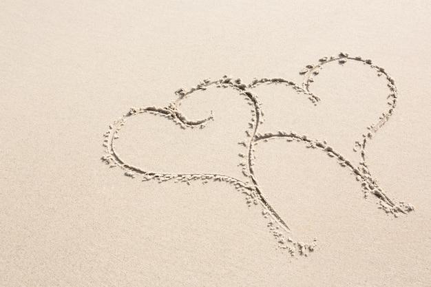 Duas formas do coração desenhado na areia Foto gratuita