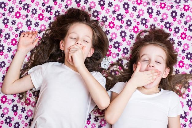 Duas garotas acordando bocejando e um despertador no meio. vista do topo Foto Premium