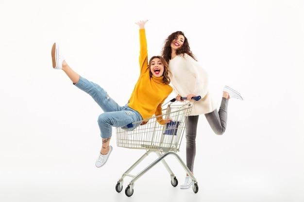 Duas garotas alegres em blusas se divertindo junto com o carrinho de compras Foto gratuita