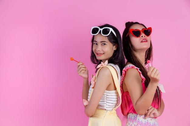 Duas garotas asiáticas amigas são felizes e têm um rosa. Foto gratuita