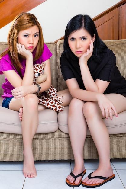 Duas garotas asiáticas em casa sendo entediado ou triste Foto Premium