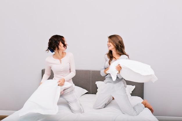 Duas garotas bonitas de pajams tendo guerra de travesseiros na cama. eles estão rindo um para o outro. Foto gratuita