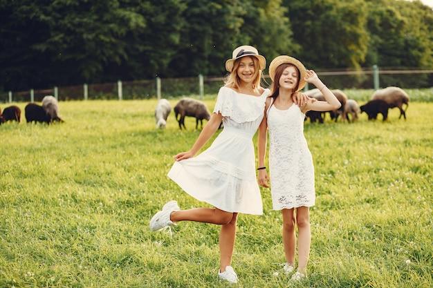 Duas garotas bonitas em um campo com uma cabras Foto gratuita