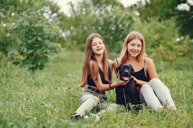 Duas garotas bonitas em um parque de verão com um cachorro Foto gratuita