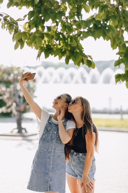 Duas garotas bonitas passeando no parque tirando fotos de si mesmas ao telefone Foto gratuita