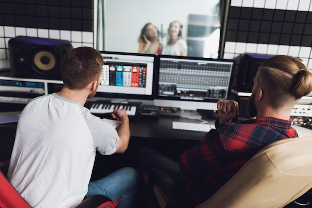 Duas garotas cantam no estúdio de gravação. Foto Premium
