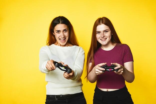 Duas garotas caucasianas sorridentes com joystick sem fio Foto gratuita