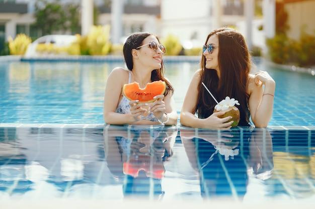 Duas garotas curtindo e comendo frutas à beira da piscina Foto gratuita