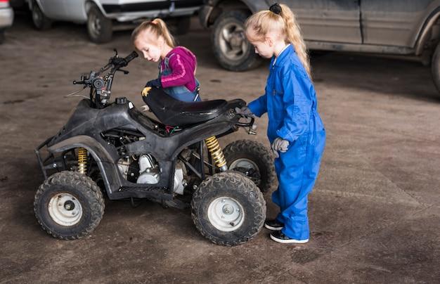 Duas garotas de macacão inspecionando moto-quatro Foto gratuita