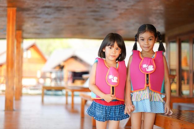 Duas garotas em fato de banho e colete salva-vidas segurar a mão juntos Foto Premium