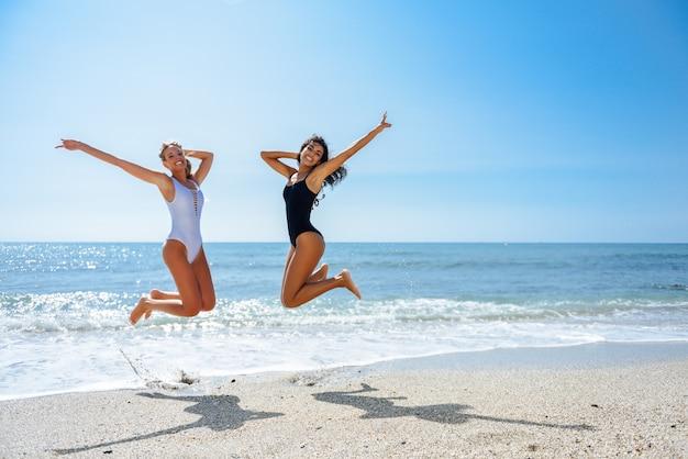 e73815b082e4 Duas garotas engraçadas em traje de banho pulando em uma praia tropical  Foto Premium