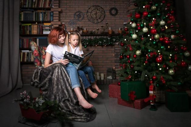 Duas garotas estão lendo um livro em uma poltrona. árvore de natal. o quarto está decorado para o natal. Foto Premium