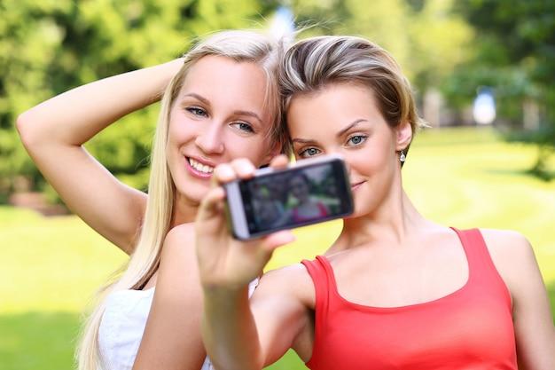 Duas garotas estão tirando fotos de si mesmas Foto gratuita