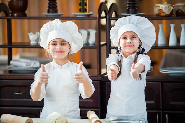 Duas garotas fazem massa de farinha. Foto Premium