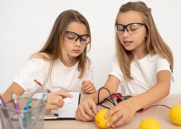 Duas garotas fazendo experimentos científicos com limões Foto gratuita
