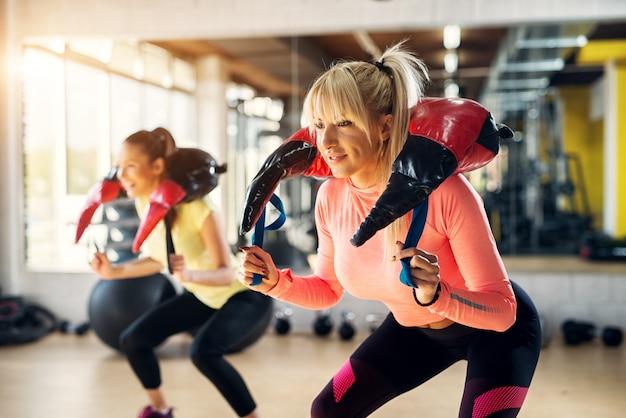 Duas garotas focadas em forma fazendo agachamentos com equipamentos de musculação em volta do pescoço. Foto Premium