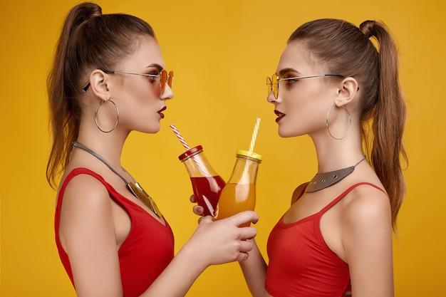 Duas garotas gêmeas hipster de glamour elegante em top vermelho moda com bebida cocktail Foto Premium
