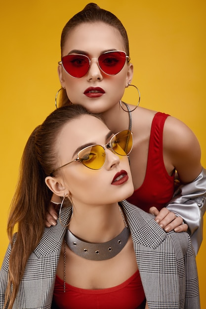 Duas garotas gêmeas hipster glamour elegante em moda top vermelho, calções pretos Foto Premium