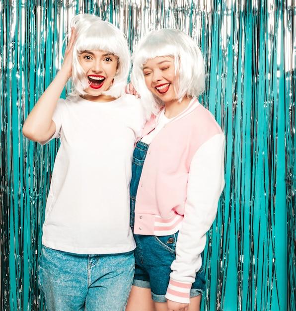 Duas garotas hipster sorridentes sexy jovem de perucas brancas e lábios vermelhos. mulheres na moda bonitas no verão de roupas de verão Foto gratuita