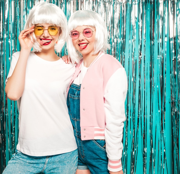 Duas garotas hipster sorridentes sexy jovens em perucas brancas e lábios vermelhos. belas mulheres na moda em roupas de verão. mostrar línguas em copos Foto gratuita