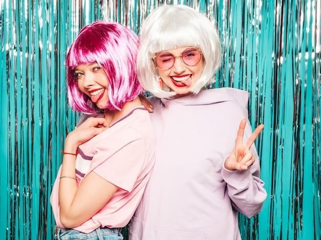 Duas garotas hipster sorridentes sexy jovens em perucas brancas e lábios vermelhos. mulheres bonitas na moda em roupas de verão Foto gratuita