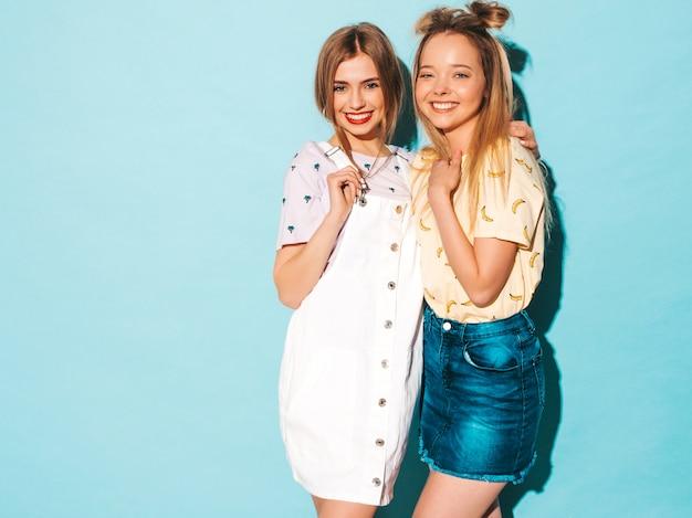 Duas garotas loiras hipster sorrindo lindas jovens em roupas de camiseta colorida na moda verão. e abraçando Foto gratuita